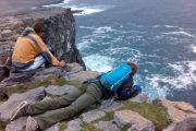 two adventure travelers looking over the cliff edge on Aran Islands