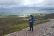 Solo traveler hiking up Croagh Patrick and overlooking Clew Bay, Westport, County Mayo