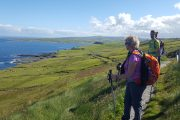 senior traveler enjoying the views on a small group hiking tour to the Cliffs of Moher, Doolin, Ireland