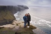 Happy friends on our Irish Experience Tours , standing on the edge of the Cliffs of Moher , Ireland