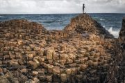 Solo traveler taking in the fresh sea air at the Giants Causeway