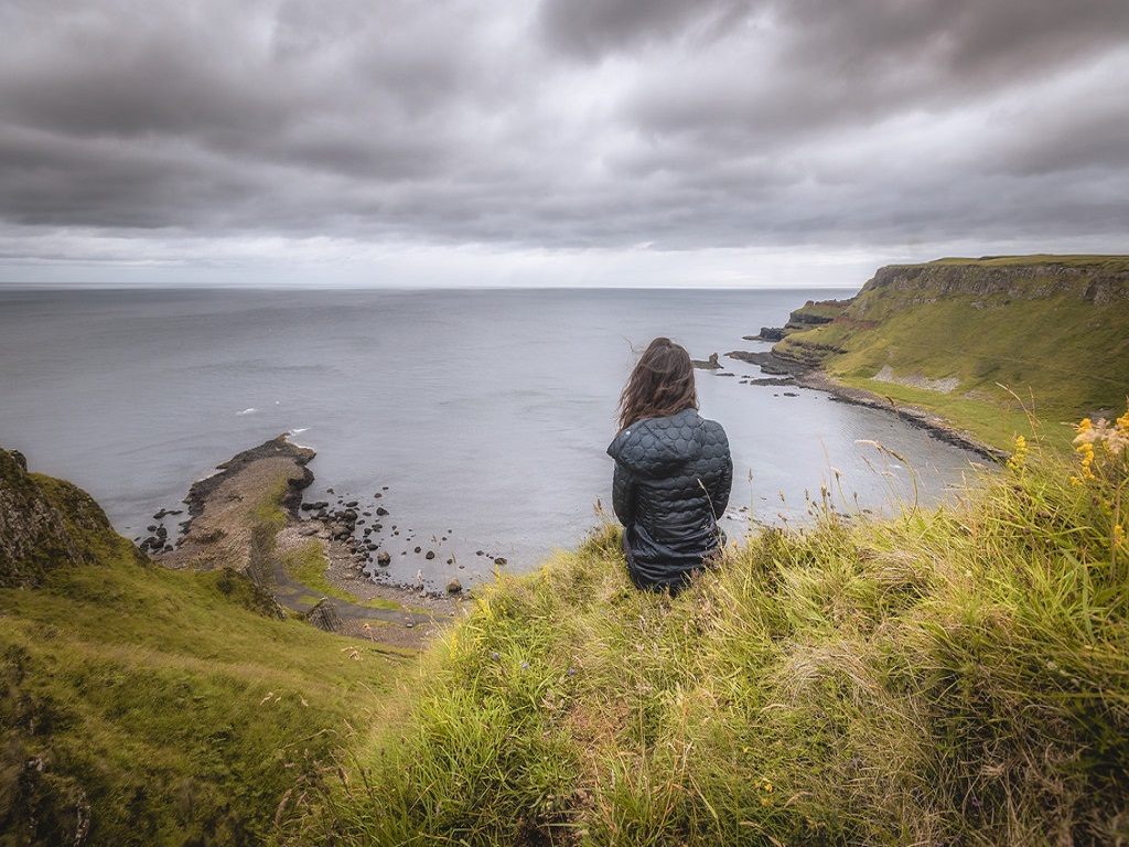 solo traveler overlooking the Giants Causeway from above