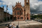 A couple on walking tour of Derry , taking a photo of The Guildhall