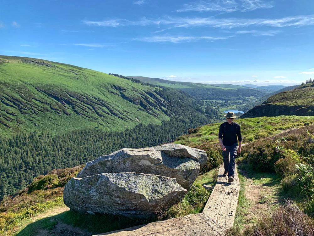 man hiking on the board walk in a sunny Glendalough