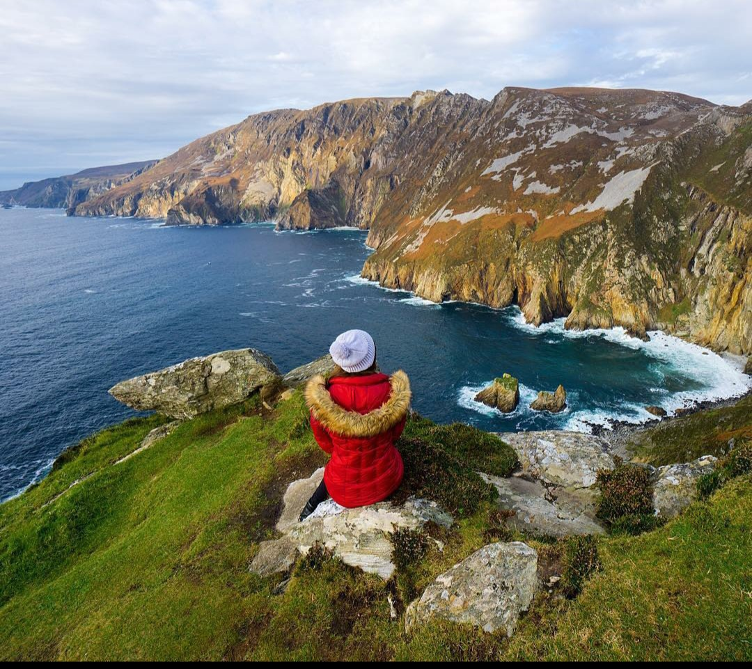 Girl in red jacket and white hat sitting on cliff edge overlooking Sliabh Liag